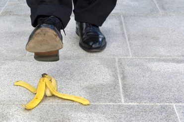 Businessman stepping on banana skin, copy space